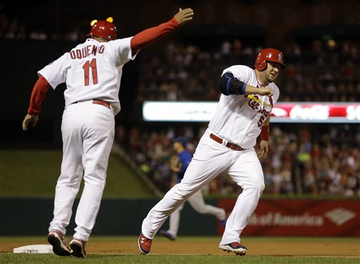 St. Louis Cardinals Third-base coach Jose Oquendo waves home Matt Adams